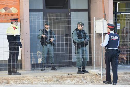 Agentes de la Guardia Civil y de los Mossos hacen guardia en un...