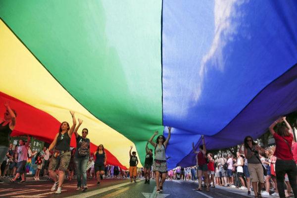 Varias personas portan una bandera arco iris gigante.