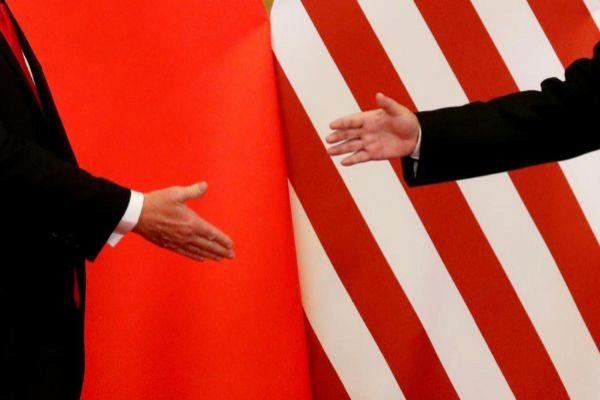 Las manos y las banderas del presidente de EEUU, Donald Trump, y de China, Xi Jinping.