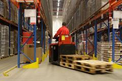 Un operador maniobra dentro de un almacén logístico
