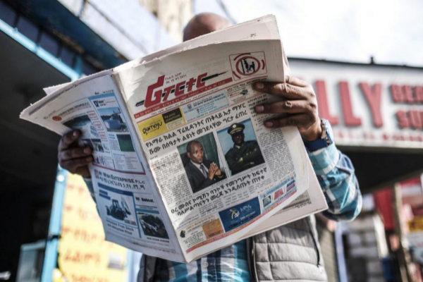 Un hombre lee 'The Reporter', que muestra en portada las fotos de Ambachew Mekonen y de Sere Mekonen, fallecidos en el intento golpista.