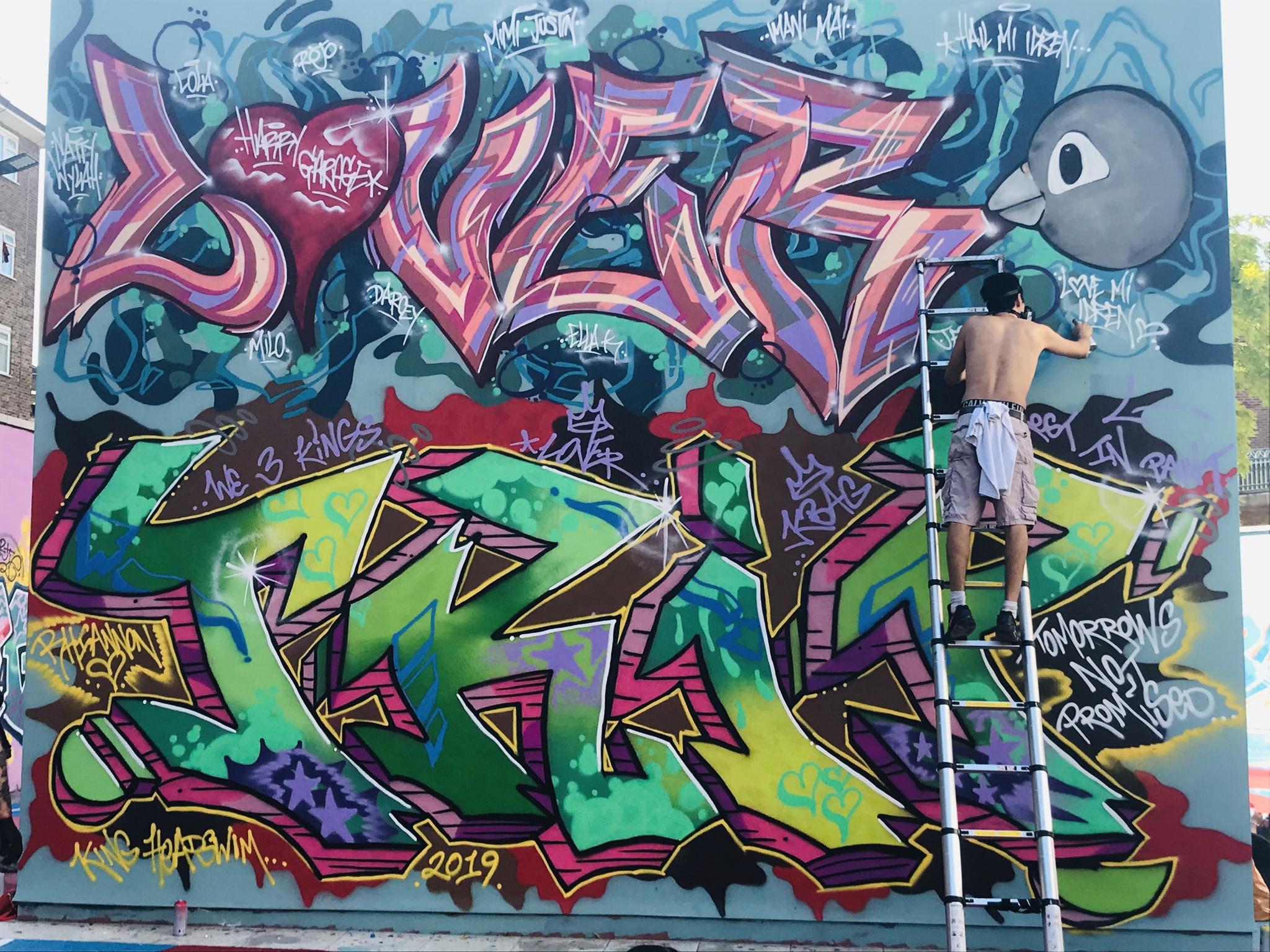 Grafiti finalizado con los nombres en grande de Lover y Trip. Uno de los autores desciende por la escalera, en primer plano otro con su cuerpo tatuado casi por completo.