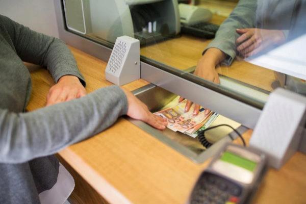 Un cliente retira dinero de una ventanilla bancaria.