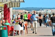 Turistas nacionales e internacionales paseando por Playa de Palma.