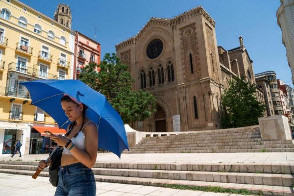 Una mujer se protege del sol con un paraguas en Lleida por la ola de...