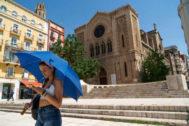 Una mujer se protege del sol con un paraguas en Lleida por la ola de calor