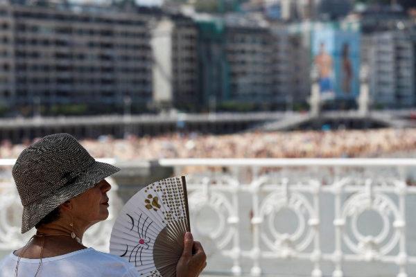 Una mujer combate la ola de calor con su abanico junto a la playa de...