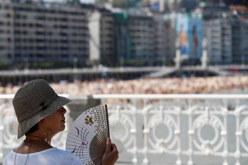 Una mujer combate el calor junto a la playa de La Concha de San Sebastián