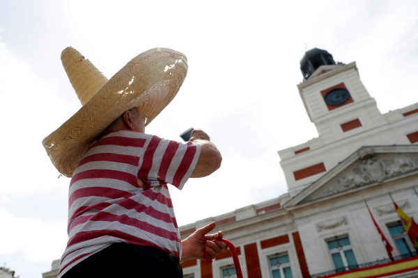 Un hombre se protege del calor en la Puerta del Sol, en Madrid.