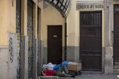 """Un hombre sin techo durmiendo en la puerta de un comedor llamado """"Ave Maria"""" situado junto a un cine en la calle Cortezo de Madrid."""