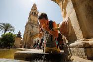 Un turista se refresca en una fuente junto a la Mezquita de Córdoba.