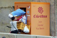 Dos personas recogen ropa de un contenedor de Cáritas, en Valencia.