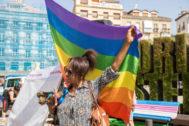 Una mujer en el centro de Vitoria con la bandera arco iris.