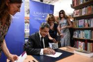 El ex presidente francés Nicolás Sarkozy firma su libro, acompañado de su esposa, Carla Bruni.