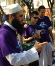 Con barba y taqiyah (gorra de oración), el catalán converso Yusuf (Carlos) Soldado, leyendo el Corán delante de una familia en un parque de Mataró.