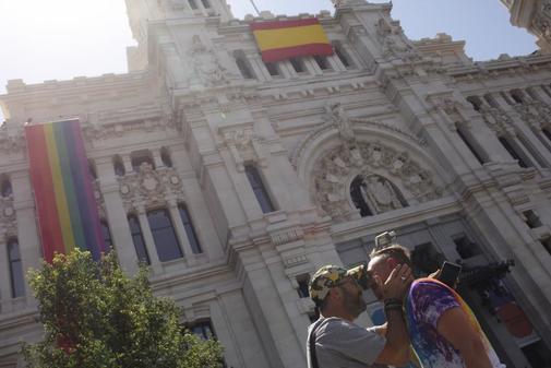 Una pareja se besa ante la fachada del Ayuntamiento de Madrid.