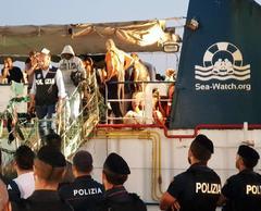 Migrantes que estaban a bordo del Sea Watch desembarcan, en Lampedusa.
