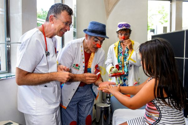 El doctor Diego de Sotto, jefe de servicio de Clínica Rotger con los payasos de la Sonrisa Médica en la Escuela de Protección Solar de Clínica Rotger.
