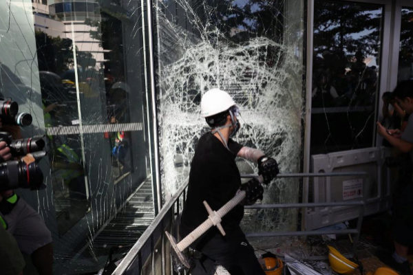Un manifestante rompe una cristalera del Consejo Legislativo en Hong Kong.