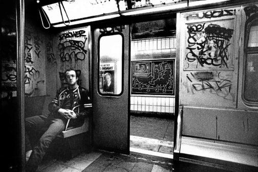 Haring sentado en el metro después de terminar una de sus obras.