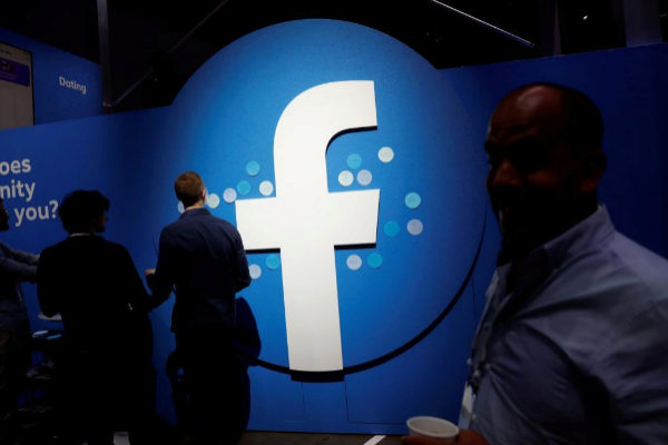 FILE PHOTO: Attendees walk past a <HIT>Facebook</HIT> logo during...