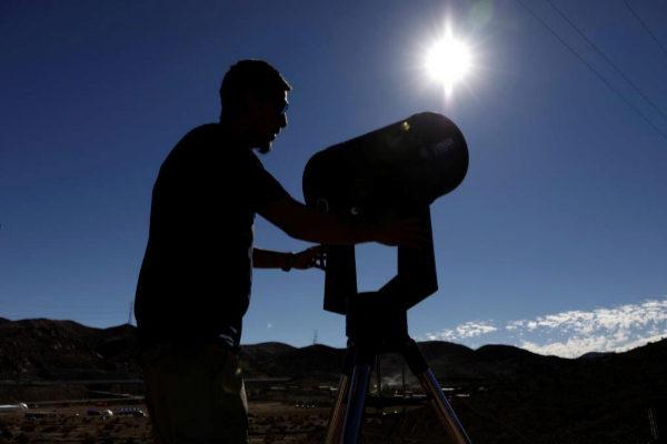Un hombre se prepara para observar el eclipse solar en Chile