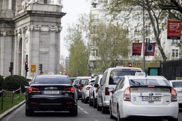 Un vehículo con licencia VTC circula junto a un taxi en Madrid.
