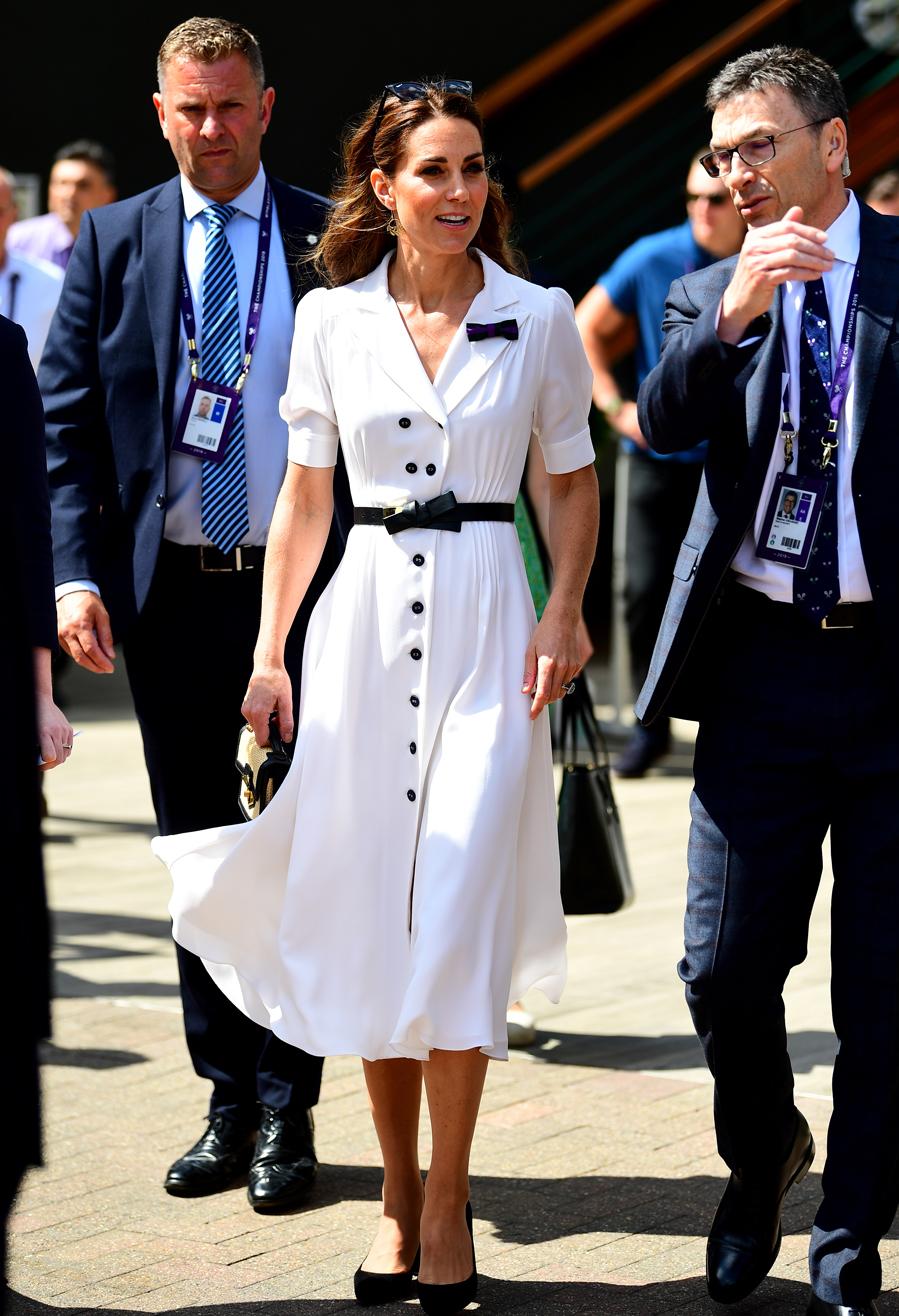 La duquesa de Cambridge tiene claro el protocolo para cada evento, y una vez más ha vuelto a dar en el clavo con un look perfecto en Wimbledon, con un vestido camisero midi en blanco con cinturón y broche con forma de lazo en negro, de Alexander McQueen, que ha combinado con un bolso mini de rafia con ribetes en negro, también de la firma, y stilettos con tacón ancho negros de ante, un básico en su armario.