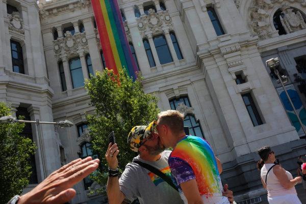 Una pareja se besa ante la bandera gay desplegada en Cibeles.