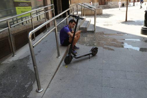 Un usuario de patinete eléctrico, junto al suyo estacionado en el centro de Castellón.