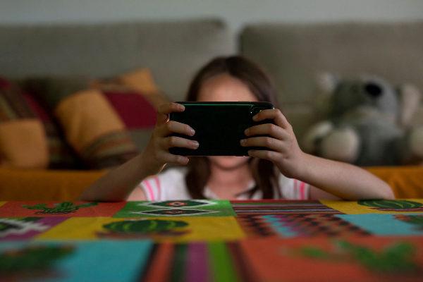Una niña usando Internet a través de un móvil.