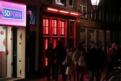 Fotografía de archivo en la que varias personas re aglomeran ante un escaparate de un burdel del Barrio Rojo de Ámsterdam, en Holanda.