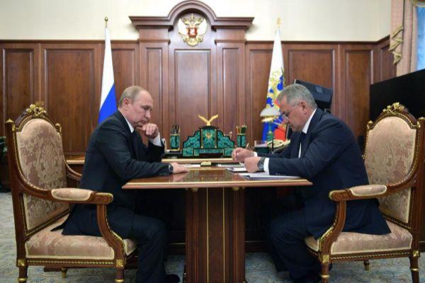 Vladimir Putin (i), escucha un informe del ministro de Defensa, Sergei Shoigu (d), sobre el minisubmarino.