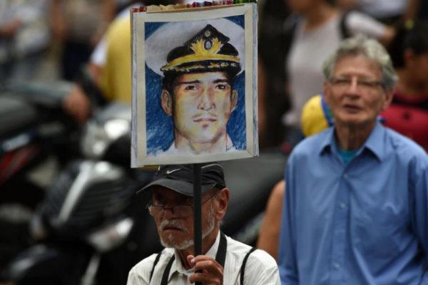 Un hombre sostiene un cartel con la cara del capitán Acosta, torturado y asesinado.