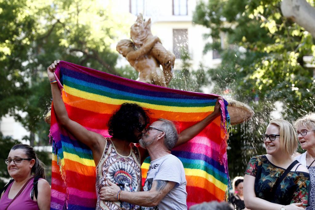 Una pareja se besa bajo una bandera arcoíris.