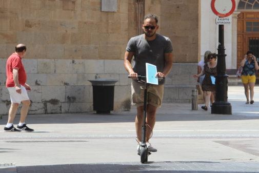 Un hombre conduce un patinete por el centro de Castellón.