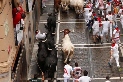 Un corredor cae en el primer encierro de San Fermín, en Pamplona.