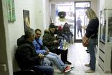Varios inmigrantes esperan en el local de una asociación de ayuda a venezolanos que llegan a España.