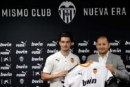 Jason sostiene la camiseta del Valencia junto al presidente Anil Murthy.