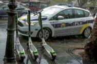 Un coche de la Policía Local junto a tres patinetes de alquiler de la empresa Lime.