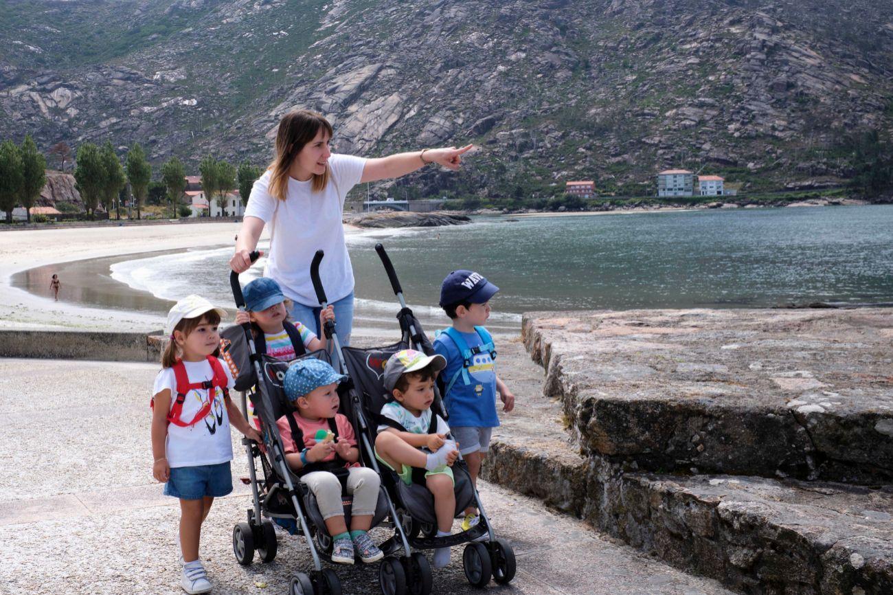Rocío Alonso y los cinco niños van a pasear por el pueblo de Ézaro. Primero juegan en el parque y después se dan una vuelta por el paseo marítimo.