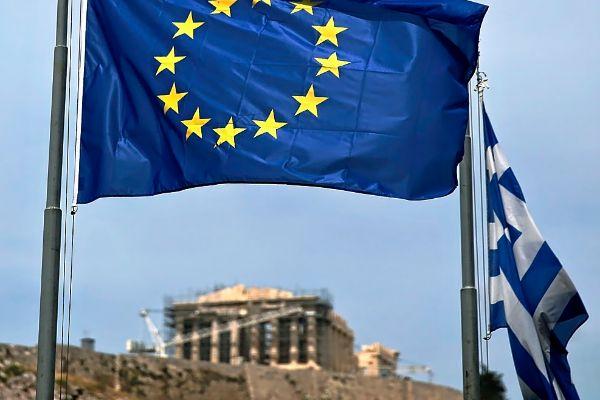 Una bandera de la UE y otra griega ondean con el Partenón de fondo.