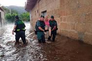 Dos guardias civiles trasladan en brazos a una mujer de Infesta, en Monterrei (Ourense), tras la riada.