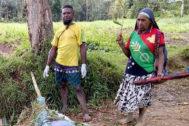 Dos personas vigilan los cuerpos tendidos de dos de los fallecidos (fuera de cuadro) en el ataque, en Paúa Nueva Guinea.