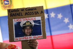 A woman shows a placard with a picture of <HIT>Rafael</HIT> <HIT>Acosta</HIT>, after a news conference in Caracas
