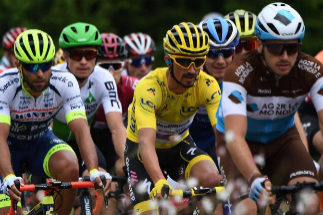 France's Julian Alaphilippe (C), wearing the overall leader's yellow jersey rides in the pack during the sixth stage of the 106th edition of the <HIT>Tour</HIT> de France cycling race between Mulhouse and La Planche des Belles Filles, on July 11, 2019. (Photo by Anne-Christine POUJOULAT / AFP)