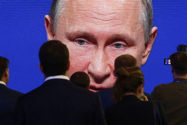 Participantes en un foro atienden la intervención a través de una pantalla del presidente ruso, Vladimir Putin, en San Petersburgo.