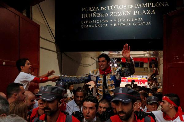 Un niño felicita a Cayetano en su salida hombros por la puerta del encierro en la plaza de Pamplona.
