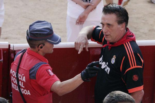 El actor Daniel Baldwin conversa con un policía foral durante el encierro de este sábado en Pamplona.
