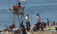 Dos vendedores ambulantes se encuentran frente al socorrista en la playa de la Barceloneta (Barcelona).
